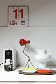 Arrangement of various kitchen accessories; retro coffee machine, set of colourful dishes and fifties-style jug on white worksurface below red and white wall calendar