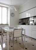Modern dining table and chairs with chrome frames in white fitted kitchen