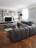 Dark grey corner sofa set and white fitted cupboards on wall of living room in traditional interior