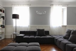 Grey sofa set in living room with traditional character and translucent curtains on windows