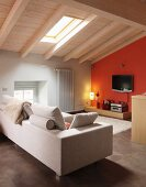 Pale sofa in attic room with wood-beamed ceiling with flatscreen TV mounted on orange wall with lamp