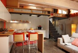 Open-plan designer kitchen with breakfast bar opposite pale sofa and staircase