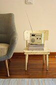 Radio and stack of books on vintage, child's chair next to arm of fifties sofa