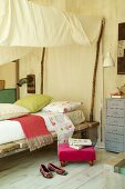 Rustic bed with improvised fabric canopy in rustic bedroom