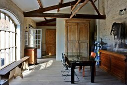 Partially renovated barn - simple furnishings in mixture of styles, modern table, wooden trunk, rustic wooden bench and lattice window