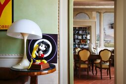 Mickey Mouse figurine and vintage lamp on side table; view into dining room with trompe l'oeil painting on wall