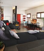 View past black sofa into open-plan interior with suspended fireplace and dining area
