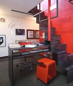Red metal chair on castors at desk integrated into metal samba staircase on red wall