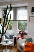 Plastic, retro bucket armchairs and tulip table in corner of room with ceiling-high cactus