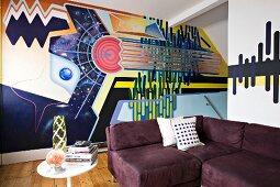 Bold, stylish mural behind aubergine corner sofa and vintage side table