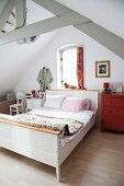 Rustic sleigh bed with white wooden frame in simple attic room with exposed wooden roof structure