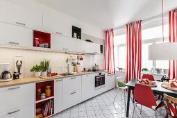 A renovated living-kitchen area with white cupboards, red-and-white striped curtains and a dining area