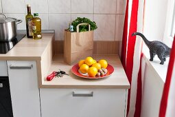 A kitchen unit with a wooden work surface next to a window with red-and-white striped curtains