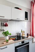 Detail of a kitchen counter with an induction hob with white wall cupboards above it in a renovated kitchen