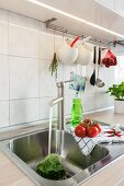 A stainless steel sink with kitchen utensils hanging above it on a pole in a renovated kitchen