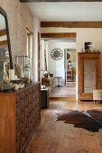 Animal-skin rug on wooden floor in rustic interior with stone wall, chest of drawers and view through open doorways
