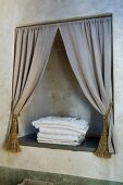 Niche with draped curtains in bathroom wall patinated with raw umber