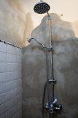 Retro Duscharmatur an einer patinierten, mit wasserabweisendem Harz verputzten Wand aus organisch geformten Wandelementen
