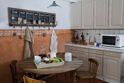 Mediterranean country-house kitchen counter with grey cupboards and white tiles, dining table, wooden chairs, and chalkboard calender above terracotta dado