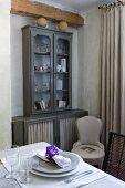 Holzbalken über grau lackiertem Geschirrschrank mit Türfüllungen, davor Polsterstuhl und gedeckter Tisch