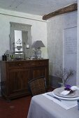 Old cabinet with mirror on top and set table in whitewashed dining room