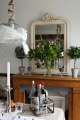 Antique mirror and vase of peonies on console table; bottles of wine in vintage bottle carriers on set table