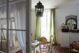 Table and wooden chairs next to window with green, floor-length curtains in rustic interior