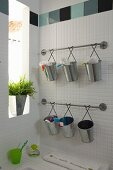 Bathroom utensils in zinc buckets hanging from rods on wall and potted plant in narrow window