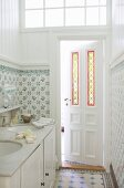 Twin washstand in narrow bathroom with traditional tiles and stained glass elements in panelled door