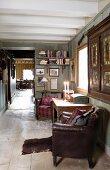 Braune Ledersessel neben Holztisch vor Wand in offenem Raum eines rustikalen Holzhauses
