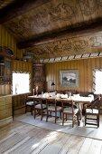 Esszimmer mit gedecktem Tisch und bemalter Holzdecke im alten Holzhaus