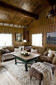 Gemütliche Sitzecke, Polsterhocker und Sofas um Couchtisch in rustikalem Wohnzimmer eines Holzhauses