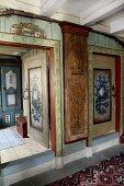 Vorraum mit bemalten Wänden in altem Holzhaus, Blick durch offene Tür auf Schrank