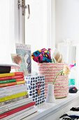 Stacked books, decorative storage box and woven basket on windowsill