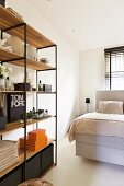 Retro shelving with black metal frame and wooden shelves in front of box-spring bed in bedroom