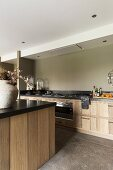 Kitchen island with black worksurface opposite counter in modern country-house style