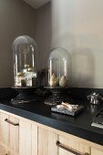 Collectors' items under glass covers on kitchen counter with black worksurface