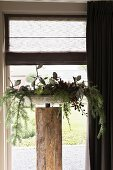 Festively decorated bowl on wooden plinth in front of window with Roman blind