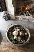 Christmas arrangement in wooden bowl on rustic table and pig ornament next to open fire in fireplace