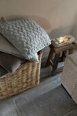 Stack of cushions with grey and brown covers in basket and narrow wooden stool on grey tiled floor