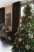 Decorated Christmas tree in room with brown floor-length curtains on windows