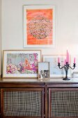 Pink candles in candelabra next to framed pictures on top of retro sideboard