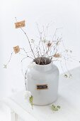 Tiny paper notes stuck on snowberry twigs in white, retro, ceramic jar