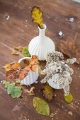 Autumn leaves in white ceramic vases and scattered on wooden surface