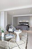 Couchtisch mit verchromtem Metallgestell neben weissem Beistelltisch und schwarzer Sessel auf Teppich, im Hintergrund Doppelbett in minimalistischem Schlafzimmer