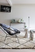 Black, retro cord easy chair and white side table on Berber rug