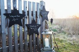 Star-shaped signs made from black-painted wooden hanging on a fence with a lantern with a candle with someone walking in the background