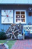 Homemade snowflakes made from silver birch against a grey-painted wooden house in the evening