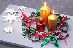 Weihnachtlicher Kranz aus Plätzchenausstechern und Schleifenbändern und drei Kerzen