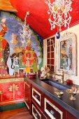 Orientalische Malerei an Wand in traditioneller Küche, filigrane Kronleuchter mit Glasschmuck über Küchenzeile